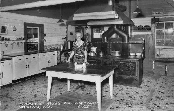 Virginia Ross poses at a table in front of a large stove in the kitchen at Ross's Teal Lake Lodge.