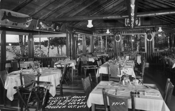 The dining room at Syd's Resort of the Woods, which shows tables set for a meal. Large picture windows have views of the lake and woods surrounding the resort, and above the windows are a number of mounted fish and  two deer heads.