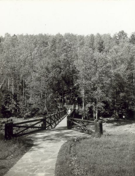 Two people on a rustic bridge over Bad River at Copper Falls State Park.
