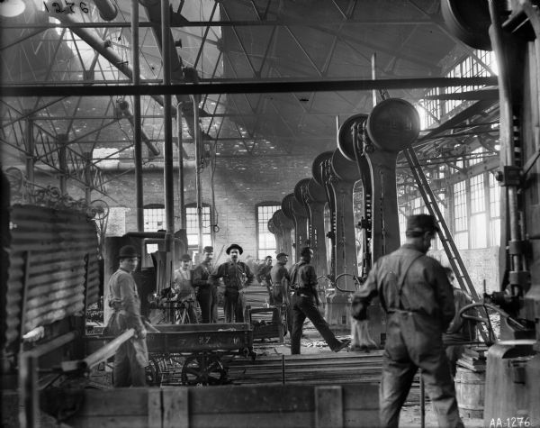 "Men working in the forge shop of the McCormick Reaper Works. The factory was owned by the McCormick Harvesting Machine Company. In 1902 it became the McCormick Works of the International Harvester Company. The factory was built in 1873 and was located at Blue Island and Western Avenues in the Chicago subdivision called ""Canalport."""