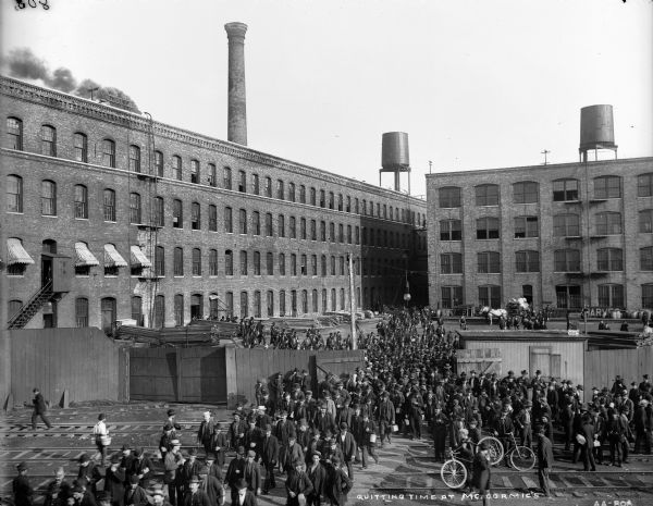 Elevated view of workers filing out of the gates of the McCormick Reaper Works at the end of a work day. The factory became part of the International Harvester Company in 1902. There are railroad tracks in front of the gates. Some of the workers carry lunch pails, and some have bicycles.