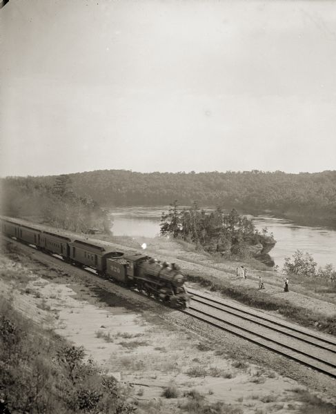Elevated view of a train running parallel to the river, past the Ink Stand. Several people are standing along the tracks and waving.