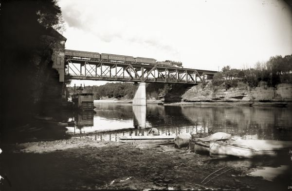 View of Kilbourn bridge with railroad train. Steamboat and rowboats at edge of river.