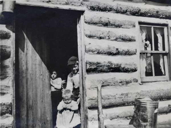 Three children peek out of the door of a log cabin. There is an ash can to the right of the door.