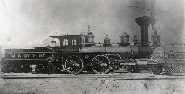 Milwaukee and St. Paul Railway locomotive no. 40, called the L.B. Rock, at the Chestnut Street yards. The mast of a ship is visible in the background, and a man poses against the coal car. There is a sign for Elmore's on the right.