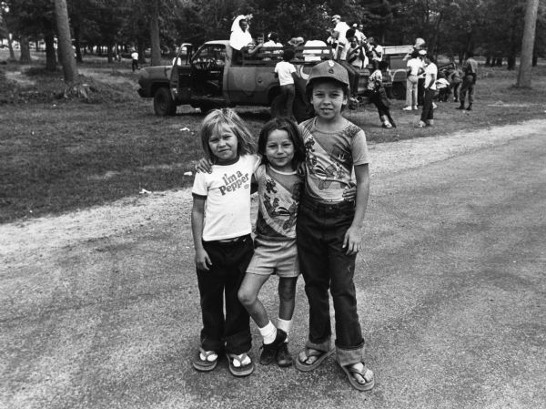 Cuban refugees at Camp McCoy. Three children standing with their arms around each others shoulders. Two wear Woody Woodpecker t-shirts, the other wears a Dr. Pepper t-shirt. In the background, a group of adults on the back of a pickup truck talk and play music. One man has a guitar.