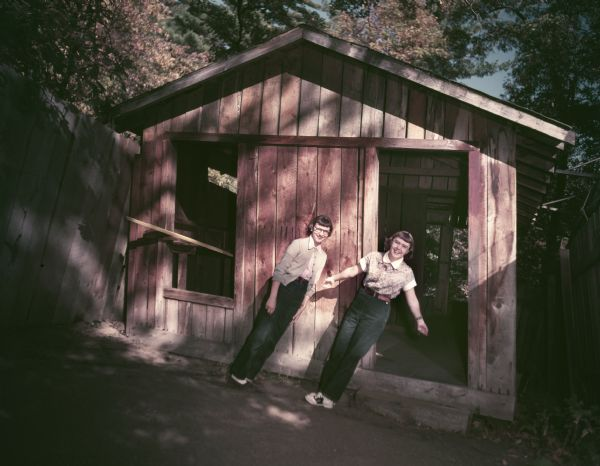 Two young women appearing to defy gravity outside a shack at the Wonder Spot.