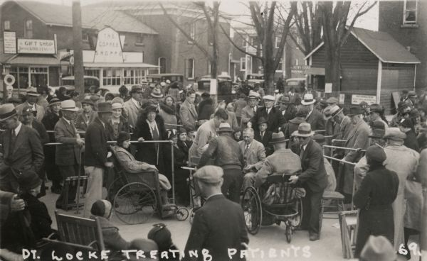 Dr. Mahlon William Locke treating arthritis sufferers on the street in Williamsburg, Ontario, Canada. Many people have gathered to watch or to receive treatment, some in wheelchairs. A coffee shop, a gift shop, and a news stand, as well as cars lining the street, are visible in the background.