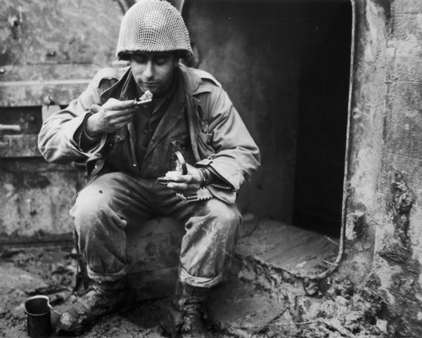 A GI of the United States 76th Infantry Division dines on K rations outside a German pillbox.
