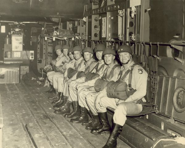 Paratroopers of the 82nd Airbourne division seated in a C-82 prior to takeoff. From right to left are Major General Ralph M. Immell (commander of the 84th Airbourne division), Colonel Edward L. Carmichael, Colonel Harold W. Gardener, Colonel Austin T. Thorson, Colonel Leslie V. Dix, Captain Clarence A. Schoenfeld, Major Patrick W. Cottber, and Major Gregory R. Endre.