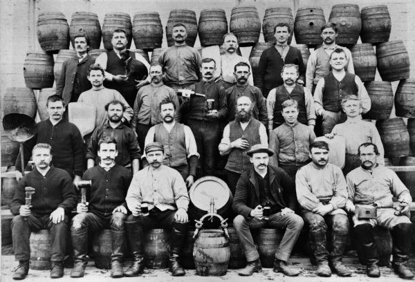 "Brewery workers, posed in front of stacked beer barrels. Pictured (2nd row, far right) is Louis Schreiber (1861-1923) who immigrated to Wisconsin from Bavaria at age 18. The tapped barrel is marked John Gund Bottling and the barrel at front center is stamped ""J.GUNDBO."""