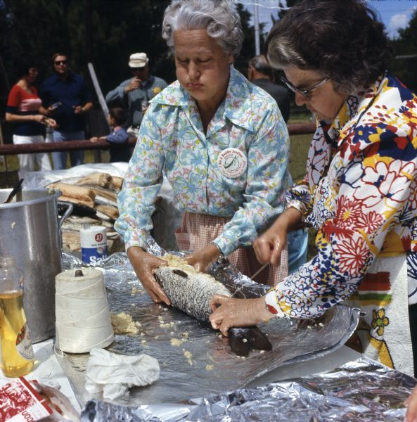 "Two elderly women are stuffing and tying a musky with string before cooking it. The women are wearing buttons with an image of a musky that reads: ""I am a Boulder Junction Rooster, 'Musky Capital of the World.'"" A group of people are watching from the sidelines."