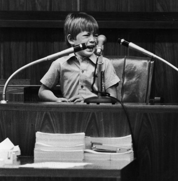 Timothy Fischer, a little boy, cries on the witness stand in a courtroom.