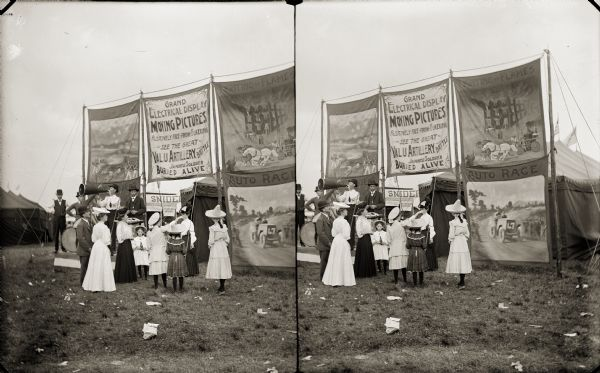 A crowd, including Evaline, Nellie and Harriet Bennett, looks at large banner advertisements for moving pictures. Moving picture subjects include fire fighting and auto races. A man with a megaphone is standing in front of the advertisements and tents.