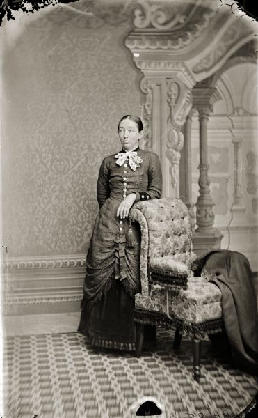 "Full-length studio portrait of Francis ""Frankie"" Irene Douty leaning on a chair in front of a painted backdrop. She was the first wife of Henry Hamilton (H.H.) Bennett."