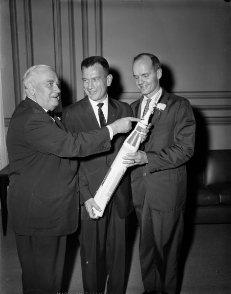 Senators Alexander Wiley and William Proxmire posing with astronaut Donald K. Slayton and a model of a rocket.