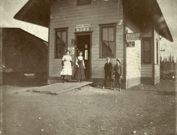 Two women and two young boys pose in front of the Koss Depot, which also serves as a post office and telegraph office.