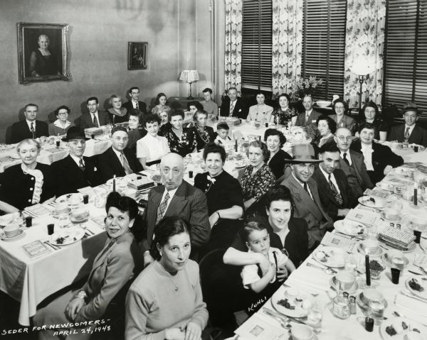A group portrait of people seated at tables for Seder. The Pelz family if identified in the lower right of the picture. The mother is identified as Esther Pelz, holding her son Harry Pelz. The father, Nathan Pelz, is to her left and is wearing a hat.