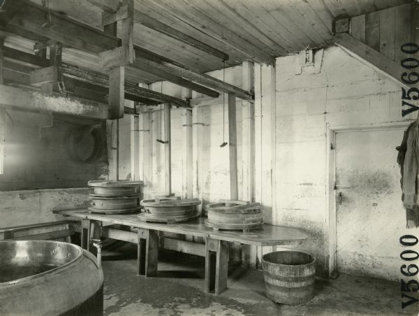 Interior view of the Jorden Prairie Cheese Factory showing Swiss cheese presses on a bench.