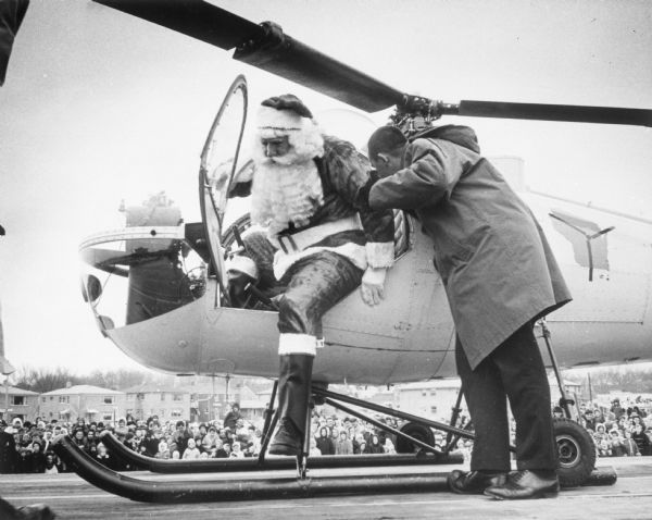 As a crowd of onlookers watch, Santa Claus alights from his special holiday helicopter with the help of an aide at Southgate Shopping Center.