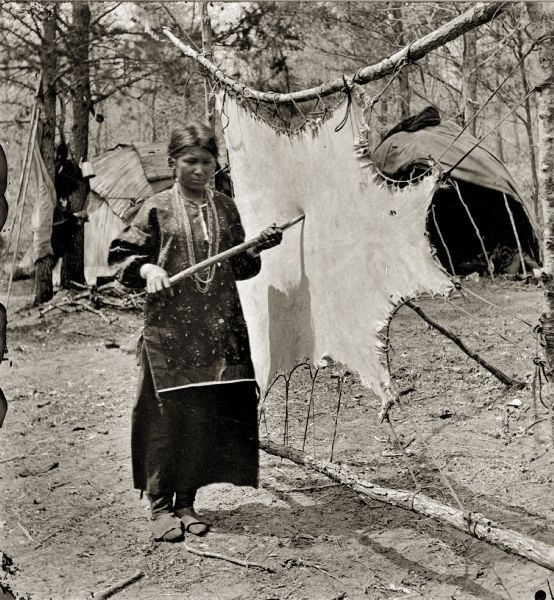 Ho-Chunk woman tanning a buckskin. Typical dwellings (chipotekes) are in the background.