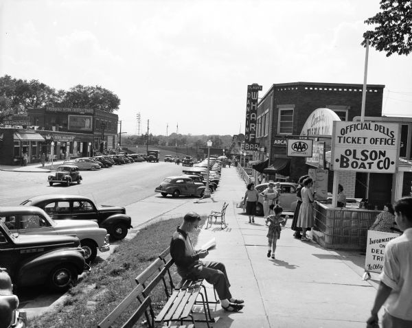 A view of downtown, including the official Dells ticket office. In the foreground a man is sitting on a bench reading a newspaper, and other pedestrians are walking along the sidewalk. There is a railroad bridge in the distance.
