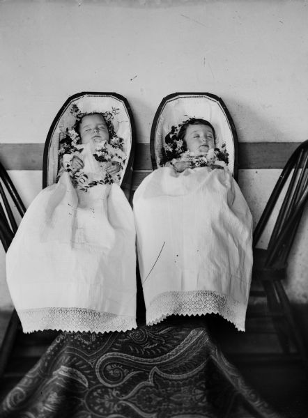 Studio portrait of deceased twin infants in coffins. They are Robert and Janet Fitzpatrick, born July 5, 1885, died April 20, 1886, children of Robert and Martha Fitzpatrick.