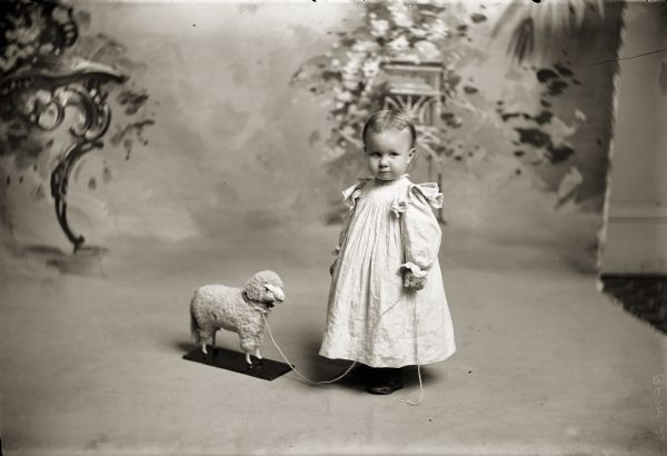 Studio portrait of Ruth Bennett with holding the string of a toy lamb standing in front of a painted backdrop.