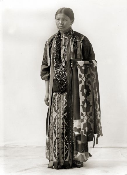 Full-length studio portrait of a Ho-Chunk Woman standing. She is the sister of Pete Pettibone.