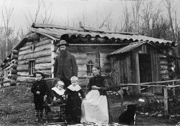 This is a family photograph of Nels Wickstrom with his wife Anna (born Anna Stoel) and their children in front of their log home. The oldest child, wearing the hat, is Nels Odin Wickstrom and the other two are Carrie and Zenella (who later married Reubin Anunson). The child with whom Mrs. Wickstrom is pregnant is Augusta Wickstrom. A dog sits nearby on the right.