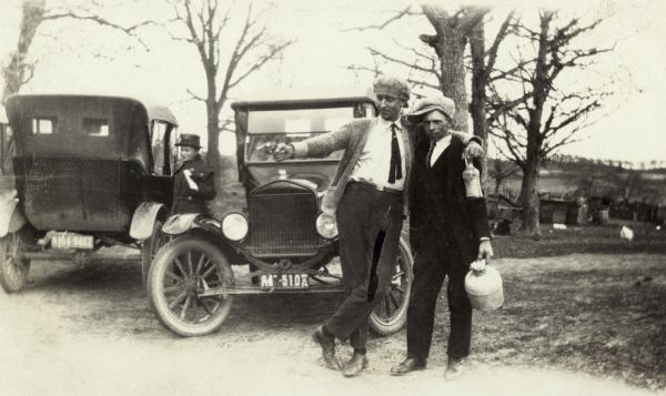 Two men standing in front of two cars, one pointing a handgun at the ground and the other looking at the camera. Each man is holding a bottle, possibly full of illegal alcohol during prohibition. There is a woman in the background between two cars.