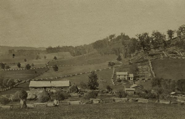 View from a distance of a farm in a valley owned by Alex(ander?) Smith. There is a wooden fence in the foreground surrounding the farm.