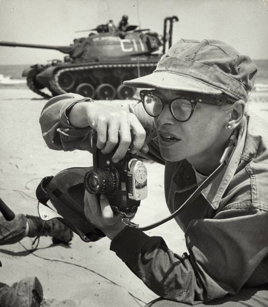 "Dickey Chapelle, photographer, on the same Milwaukee beach where she learned to swim as a young girl. She was covering ""Operation Inland Seas"" celebrating the opening of the St. Lawrence Seaway. She is holding her camera and there is a tank in the background. This is her favorite photograph of herself at work."