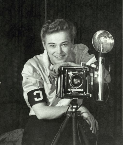 "Dickey Chapelle wearing correspondent armband and taking a self-portrait in mirror. Taken at time of her first recognition by War Department as ""Look's"" photographer."