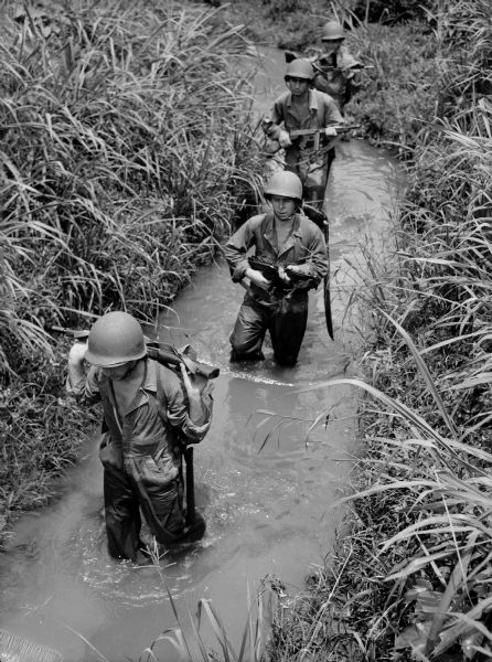 Soldiers ford a stream in Panama holding their rifles.