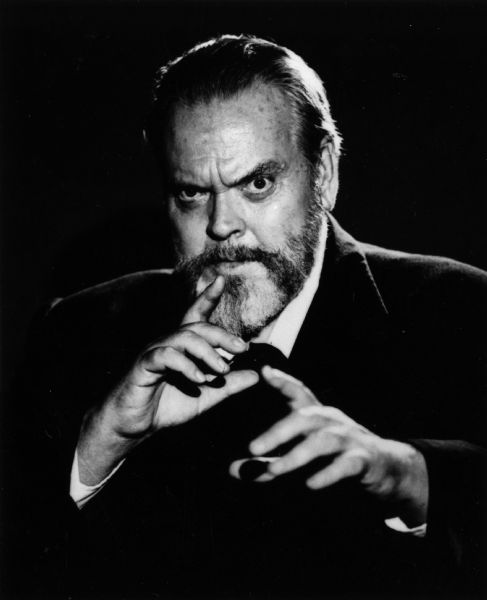 A classic Orson Welles publicity still showing him looking intensely into the camera while gesturing with his hands.