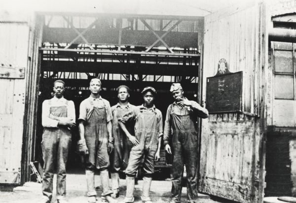 Five foundry workers at Fairbanks, Morse & Company, taking a break just outside the door of the building. Workers names: Solomon Deberry, Curtis Barber, two unidentified co-workers, and Deberry's son, Booker T. Deberry. Fairbanks, Morse and Company is best known for building engines of many kinds.