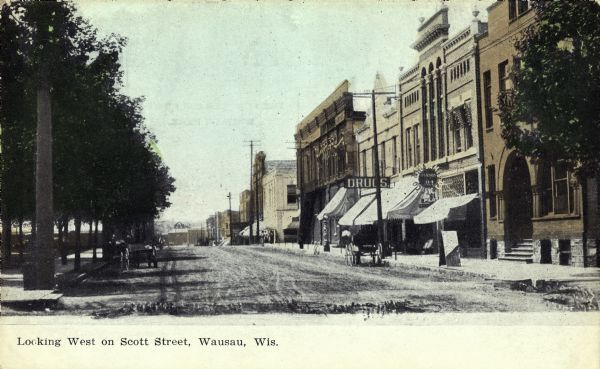 View of Scott Street, looking westward. A horse-drawn carriage is parked near a large sign for a drugstore.