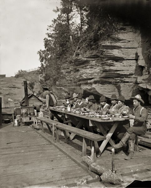Stereograph of a group of raftsmen eating at a table onboard a lumber raft near the shoreline.