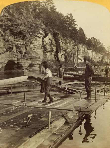 Stereograph of men working on rafts.