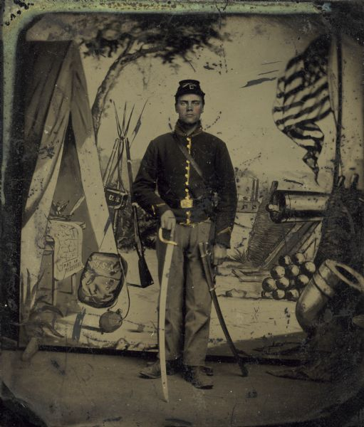 A tinted tintype of a Civil War soldier posing with an officer's sword in front of an elaborately painted studio backdrop depicting a tent, an American flag, and a cannon.  The soldier is possibly Stanley Lathrop from Montello who served in the 1st Wisconsin Cavalry.