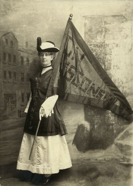 Portrait of Theodora Youmans (Mrs. Henry), President of the Wisconsin Woman Suffrage Association, holding a Wisconsin flag and standing in front of a painted backdrop.