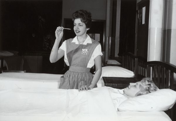 A nurse, possibly a student nurse, looks at a thermometer after taking the temperature of a female patient laying in bed.