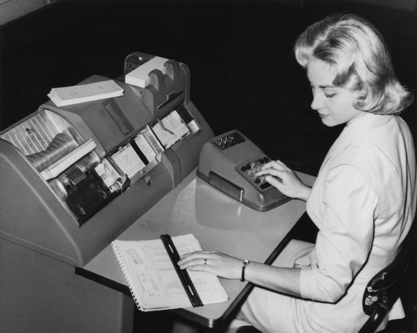 A student studies key punch operation in a data processing class at Milwaukee Vocational and Adult Schools. She is seated at a very large computer.