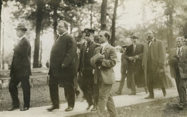 President Taft walking along a path at the Soldier's Home where he addressed veterans. Several others accompany the President, including Mayor David S. Rose, wearing a long coat and holding his hat.