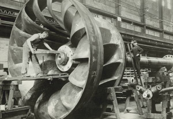 Men work on a huge, metal water wheel at Allis-Chalmers Manufacturing Company.