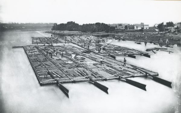 Elevated view of lumber raft and workers on the Chippewa River. In the background on the right are dwellings.