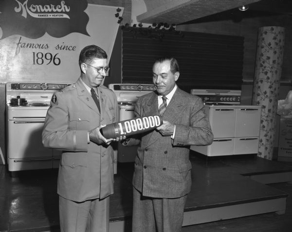 Col. Robert K. Haskell (left) receiving the one millionth shell manufactured by the Malleable Iron Range Co. of Beaver Dam in a ceremony at the manufacturing plant. H.T. Burrow (right), President of the company, presented the shell during a ceremony. Three Monarch ranges can be seen in the background.