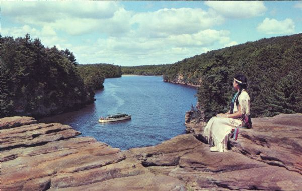 A woman in an Indian dress and headband sits at High Rock in the Upper Dells looking over the Wisconsin River at a tour boat.