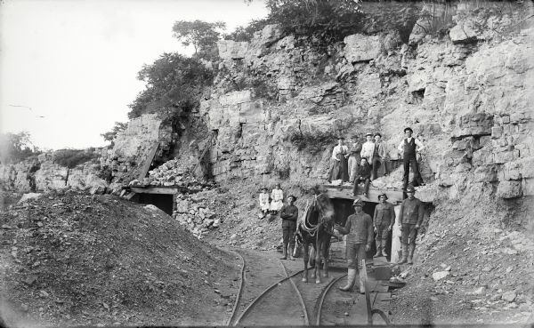 "Visitors, dressed in their Sunday best, contrast with the rough garb of the miners. Left to right, miners were: Charles Kanass, Robert ""Beaver"" Smith (holding the mule), John Smith (his brother), and Charley Klick. The man sitting directly over the mine entrance was Steve Hayes. The man in the dark business vest and white shirt (at extreme right), standing atop the entrance, was James Cundy, mine superintendent. The other men, women and children have not been identified."